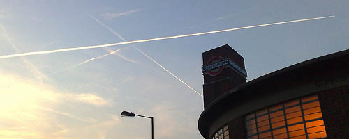 Chiswick Park tube station with contrails.